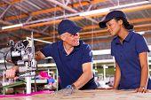 friendly senior cutter teaching young worker cutting fabric