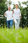 Active senior couple doing nordic walking together in summer
