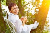 Relaxed senior woman taking a break with cup of tea in her garden