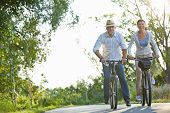 Happy senior couple riding bicycles on a bike path in summer