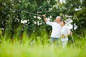 Senior couple hiking and man pointing to the distance with walking stick