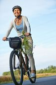 Smiling woman riding bike with helmets on a road in summer