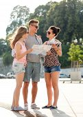 friendship, travel, tourism, vacation, summer and people concept - smiling friends with map and city guide outdoors