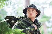war, hiking, army and people concept - young soldier or ranger with backpack in forest