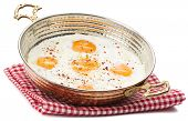 Fried egg in copper egg pan isolated on white background