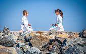 boy and girl practicing yoga on beach