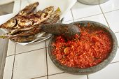 Sambal, special spicy chili paste in Indonesia, making on stone mortar to be eaten with another meal like fried fish