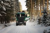 stock photo of logging truck  - Truck with log in road in forest in winter