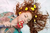 foto of have sweet dreams  - young caucasian girl lying over white linen and hair spread over the floor with flowers on it having gentle touch of sweet candy and relaxing dreaming look - JPG