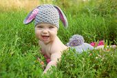 image of spring lambs  - Portrait of baby wearing like a bunny or lamb of green grass. Happy childhood outdoors.