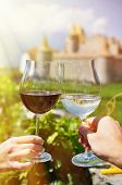 Two hands holding wineglasses against Chateau d'Aigle, Switzerland