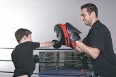 A coach with a child learning boxe