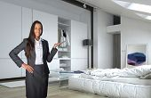 3D Rendering of Close up Young Asian Indian Female Agent Showing Architectural White Bedroom with White Furniture.