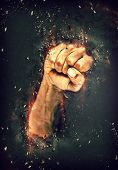 Man punching his fist through stones over a black background with in a dramatic conceptual image