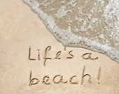 Concept or conceptual hand made or handwritten life is a beach text in sand on a beach in an exotic island