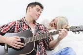 A handsome man playing guitar to a cute girl