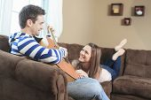 stock photo of serenade  - A Handsome man serenading his girlfriend with guitar at home in the living room - JPG