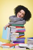 Happy smiling student girl having a break while studying surrounded by colorful books, isolated on yellow background.