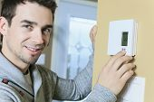 foto of carbon-footprint  - A man set the thermostat at house - JPG