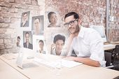 Businessman using computer at desk against profile pictures