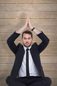 Businessman sitting in lotus pose with hands together against wooden planks