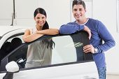 Smiling couple leaning on car at new car showroom