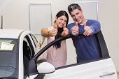 Smiling couple standing while giving thumbs up at new car showroom