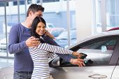 Smiling woman presenting her new car at new car showroom