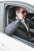 Businessman on the phone wearing sunglasses in his car