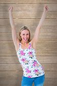 Happy blonde cheering with arms up against wooden planks