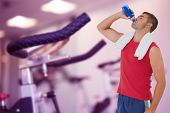 Fit man drinking water from bottle against row of exercise bikes focus on foreground