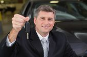 Smiling businessman holding a customer car key at new car showroom
