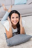 Pretty brunette lying on the rug listening to music at home in the living room