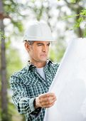Mature male architect analyzing blueprint at construction site