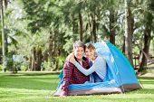 Portrait of smiling couple camping in park
