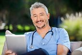 Portrait of smiling male doctor with tablet computer sitting at nursing home porch