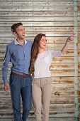 Full length of couple looking away against faded pine wooden planks