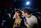 Man consoling woman crying while watching movie in cinema theater