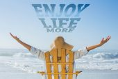 Woman relaxing in deck chair by the sea against enjoy life more