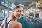 Pretty swimmer by the pool smiling at camera against empty swimming pool with large windows