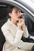 Businesswoman having a phone call while putting on lipstick in her car