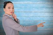 Thoughtful asian businesswoman pointing against wooden planks