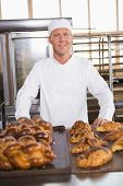 Smiling baker showing board of breads in the kitchen of the bakery