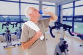 Senior man drinking from water bottle against spinning exercise bikes in gym room