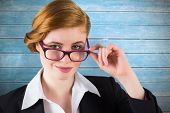 Redhead businesswoman touching her glasses against wooden planks