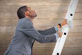 Businessman climbing up ladder against wooden surface with planks