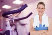 Fit woman with towel on shoulders against row of exercise bikes focus on foreground