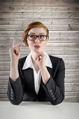 Thinking redhead businesswoman against wooden planks background