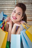 Portrait of a happy brunette holding shopping bags against wooden background in pale wood