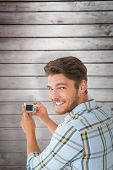 Man taking photo and smiling at camera against wooden planks